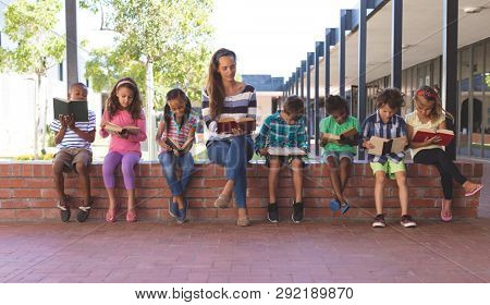 Front view of caucasian teacher and multi ethnic students reading book while sitting on brick wall at corridor in school