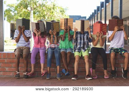 Front view of multi ethnic students hiding behind book while sitting on brick wall at corridor in school