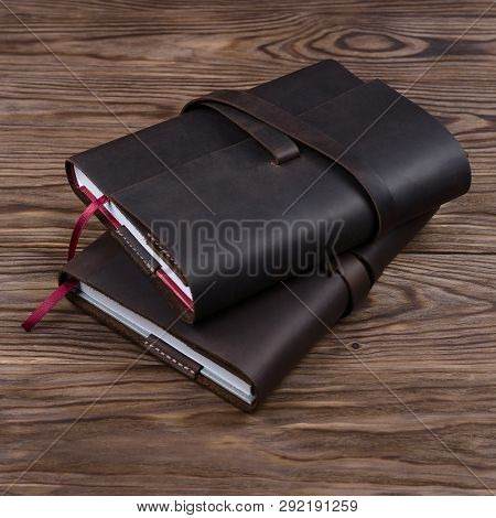 Two Brown Handmade Leather Notebook Cover With Notebook Inside On Wooden Background. Stock Photo Of