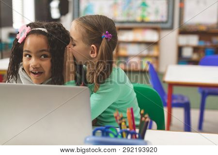 Front view of Caucasian schoolgirl whispering a secret into friend ear while her friend seem astonishied in classroom at school