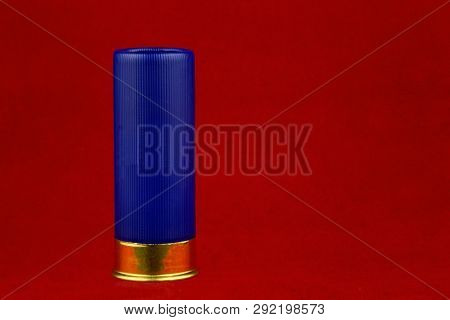 Blue shotgun cartridge isolated against a red background poster