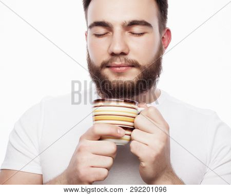 Good morning, man holding a cup tea. Morning concept. Handsome bearded male holds cup of coffee, tea. Smiling hipster man with cup of fresh coffee.  Isolated over white background. poster