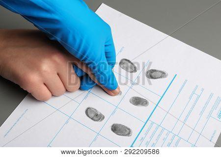 Investigator Taking Fingerprints Of Suspect At Table, Closeup. Criminal Expertise