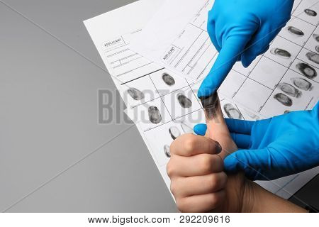 Investigator Taking Fingerprints Of Suspect On Grey Background, Closeup With Space For Text. Crimina
