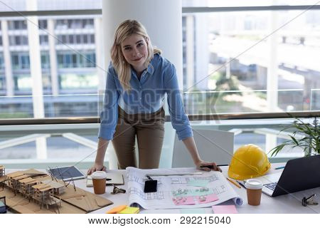 Portrait of blonde young Caucasian female architect looking at camera at desk in modern office. She is smiling