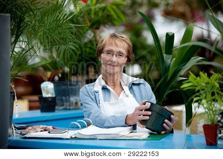 Portrait of a senior woman standing at check out counter in garden center