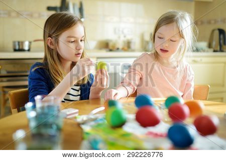 Two Cute Young Sisters Dyeing Easter Eggs At Home. Children Painting Colorful Eggs For Easter Hunt.