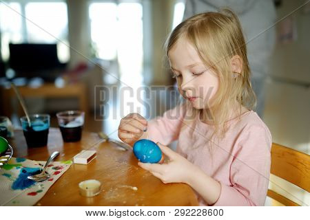 Cute Young Girl Dyeing Easter Eggs At Home. Child Painting Colorful Eggs For Easter Hunt. Kid Gettin