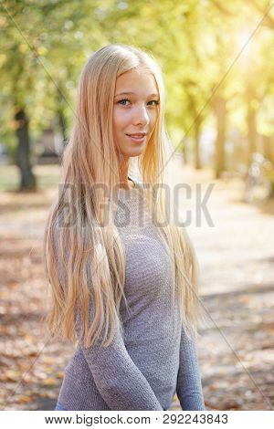 Outdoor Portrait Of Blond Young Woman Enjoying Sunny Day - Added Sun Flare Light Leak Filter