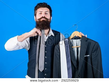 How About This Tie. Brutal Hipster Holding Colorful Tie Collection And Suit Jacket. Bearded Man Matc