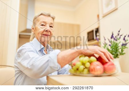 Old woman as a senior citizen in a senior citizen's home or retirement home with fresh fruit