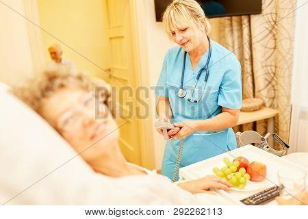 Caregiver cares for bedridden senior citizen in senior citizen's home or retirement home