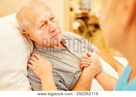 Nursing consoles a sick senior man in a nursing home or in home care