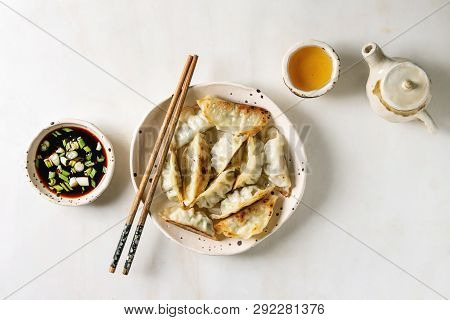 Fried Asian Dumplings Gyozas Potstickers In White Ceramic Plate Served With Chopsticks, Bowl Of Soy