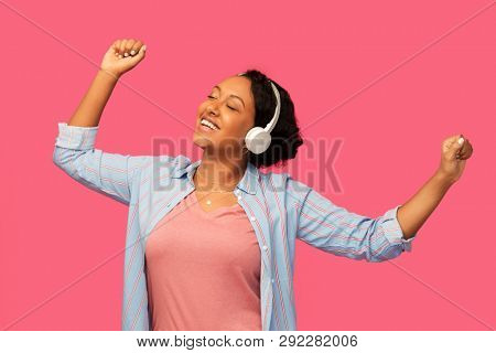 people, technology and audio equipment concept - happy african american young woman in headphones listening to music and dancing over pink background