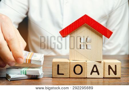 Wooden Blocks With The Word Loan, House And Money In The Hands Of A Businessman. The Concept Of Buyi