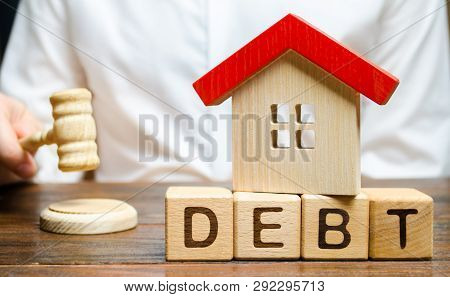 Wooden Blocks With The Word Debt And A Miniature House With A Judge's Hammer. Confiscation Of Proper
