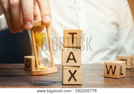 Businessman's Hand Holding A Hourglass Near The Wooden Blocks With The Word Tax. Time To Pay Taxes.