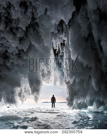 Silhouette Of A Man In A Cave Covered With Blue Ice And Icicles