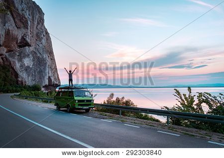 Djerdap Canyon, Serbia - 10/07/2018 - Young Girl Standing On Top Of Vintage Classic Camper Van With