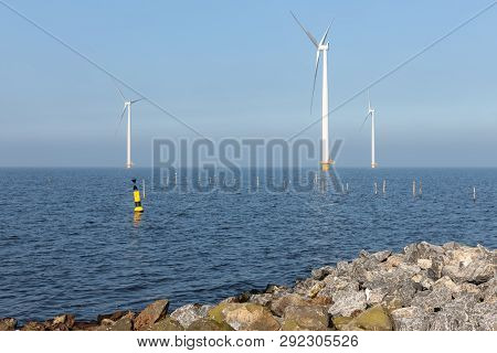 Sunny Day With Offshore Wind Turbines Near Dutch Coast With Buoy And Poles For Fishing Nets