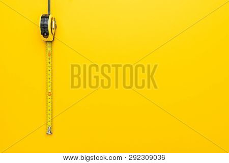 Tape Measure On The Yellow Background. Photo Of Yellow Tape Measure With Copy Space. Top View Of Met