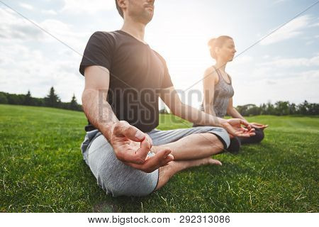 Yoga Class. Young Couple Are Meditating And Doing Yoga Exercises While Sitting In Lotus Pose On A Gr