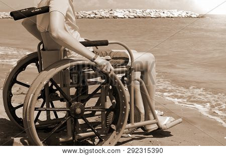 Young Boy On The Wheelchair By The Sea With Vintage Sepia Toned Effect
