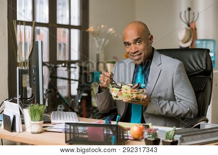 Happy Professional Man Having A Healthy Lunch In His Office