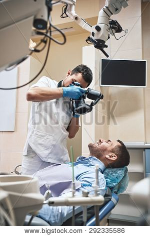 Gentle, High-quality Dental Care. Dentist With Camera Making Shots Of Patients Smile After Treatment