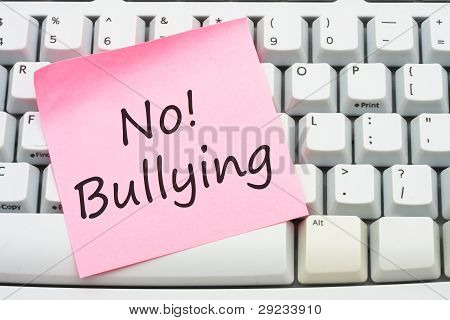A computer keyboard with a sticky note saying no bulling Stop internet bullying poster