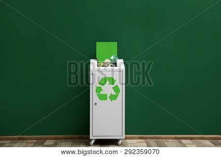 Overfilled Trash Bin With Recycling Symbol Near Color Wall Indoors
