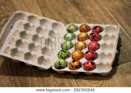 incomplete packing of colored eggs. side view. packing on a wooden floor. poster
