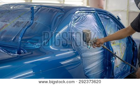 Man With Protective Clothes And Mask Painting Car Using Spray Compressor ,spay Blue Car