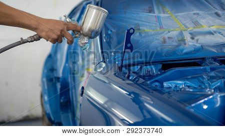 Man With Protective Clothes And Mask Painting Car Using Spray Compressor , Spay Blue Car
