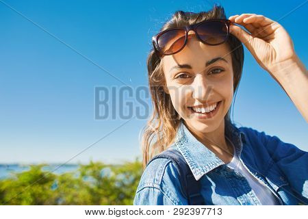 Portrait Of A Young Smiling Attractive Woman With Sunglasses At Sunny Day On The Blue Sky Background
