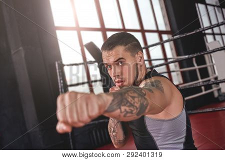 Good Jab. Muscular Athlete In Sports Clothing Throwing Jab Punch In Boxing Gym. Confident Boxer Doin