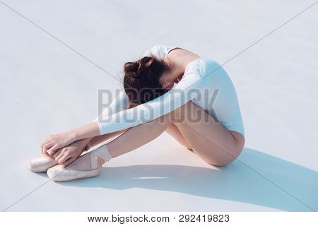Keeping Herself Fit. Pretty Woman In Dance Wear. Young Ballerina Sit On Floor. Cute Ballet Dancer. P