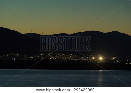 Night Scene Of Astros Town With Wind Turbines On Hills, Greece Peloponnese. Renewable Eco Energy Con