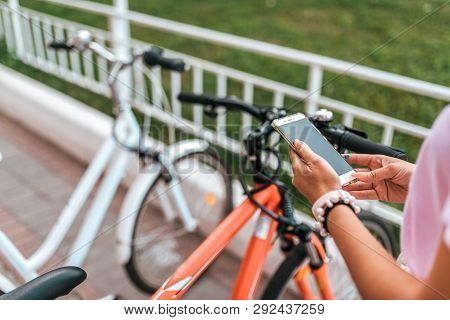 In Summer City Background Parking Bicycles, Girl Chooses Route Application, Internet Online Map Phon