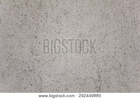 Gray White Granular Surface Of The Wall With Black Dots And A Large Crack. Rough Texture