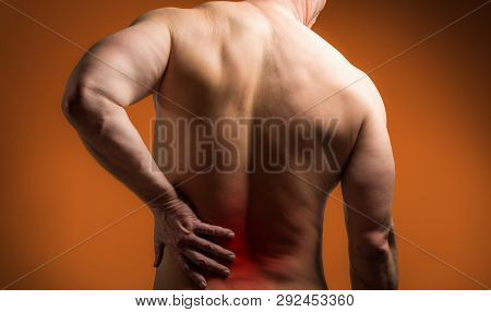 Muscle Man With Pain In His Back. Red Color Zone Is The Pain. Medical Concept On Orange Background