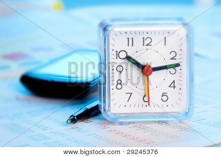 Alarm clock, cellphone, paper and ballpen