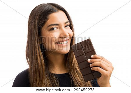 Portrait of woman tempted to have heavenly chocolate while smiling over white background poster