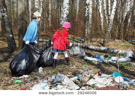 Back of brother and sister with black bags collect trash in park at spring