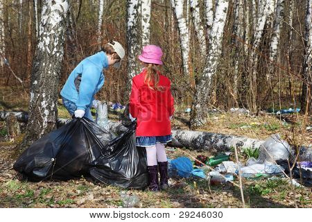 Back of brother and sister with black bags collect last year trash in park at spring