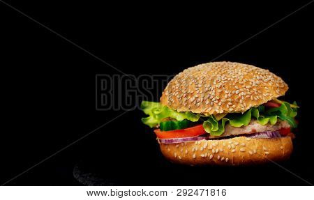Delicious Burger With Meat And Fresh Vegetables Isolated On Black Background. One Tasty Beef Mouth-w