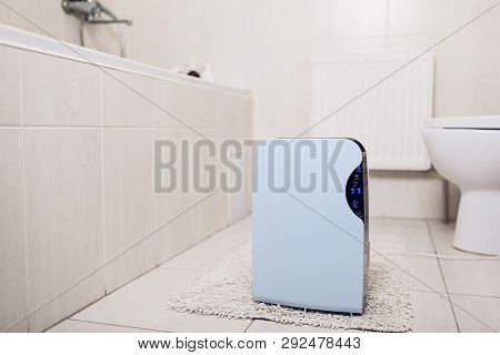 Dehumidifier with touch panel, humidity indicator, uv lamp, air ionizer, water container works in bathroom. Air dryer poster