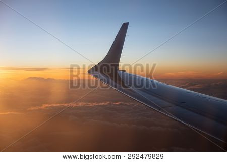 Dusk Above Clouds Through Airplane Window