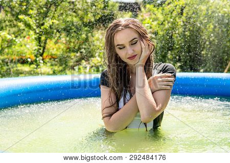 Beautiful Female Model Dressed In Long Evening Gowns, Lies In The Pool And Sensually Poses